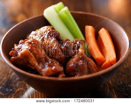 bbq sauced buffalo chicken wings in wooden bowl with celery and carrot sticks