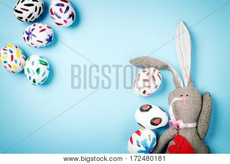 Easter bunny on a blue background. Rabbit. Easter ideas. Easter eggs. Space for text. Black lettering on a heart happy easter.
