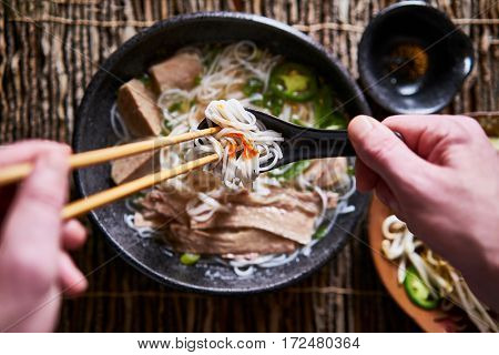 top down composition of eating vietnamese pho with chopsticks and spoon, has dab of sriracha for flavor