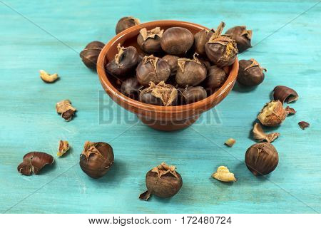 A photo of peeled and unpeeled roasted chestnuts in an earthenware bowl, on a vibrant teal blue background with copy space