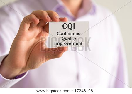 Businessman Holding A Card With Text Cqi Continuous Quality Improvement