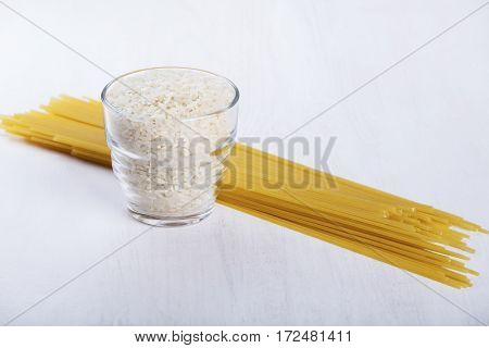 Glass of white raw rice and handful of raw spaghetti pasta