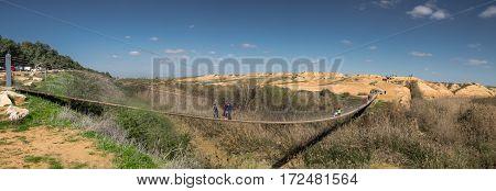 Panoramic View Of People On Suspension Bridge Over Besor River In Eshkol National Park. Negev Desert