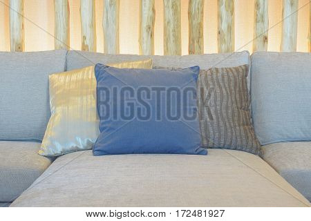 Blue Pillow Setting On Light Gray Sofa With Decorative Wooden In Background