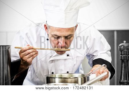 Focused chef tasting sauce with wooden spoon in professional kitchen