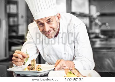 Closeup of smiling male chef garnishing food in kitchen