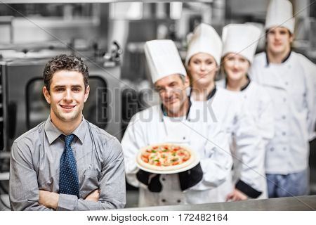 Portrait of waiter standing in front of chefs holding pizza in professional kitchen