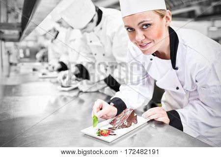 Smiling chef looking up from finishing dessert in the kitchen
