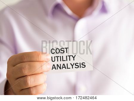 Businessman Holding A Card With Text Cost Utility Analysis
