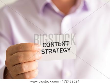 Businessman Holding A Card With Text Content Strategy