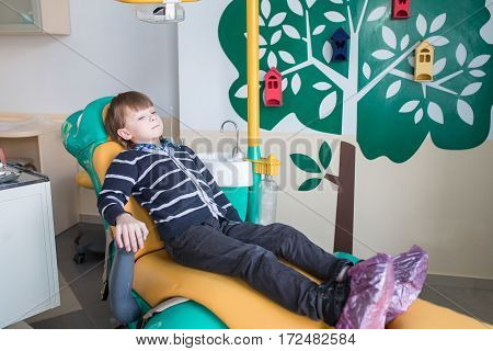 child sitting in a dental chair and waiting a doctor