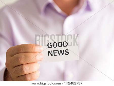 Businessman Holding A Card With Text Good News