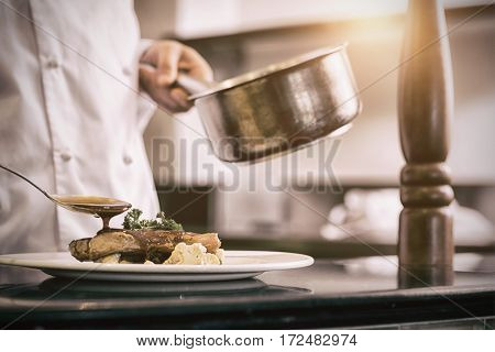 Closeup mid section of a chef garnishing food in the kitchen