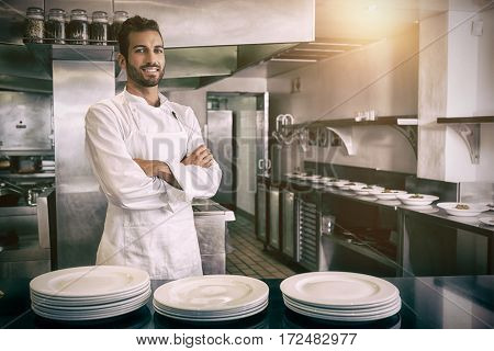 Portrait of smiling young chef standing with arms crossed behind counter in professional kitchen