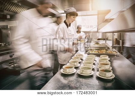 Four chefs working in a modern kitchen preparing soups and dishes