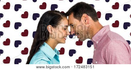Smiling couple touching foreheads against background with hearts