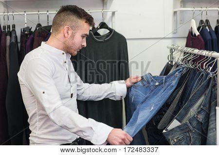 confident man choice jeans in wear shop