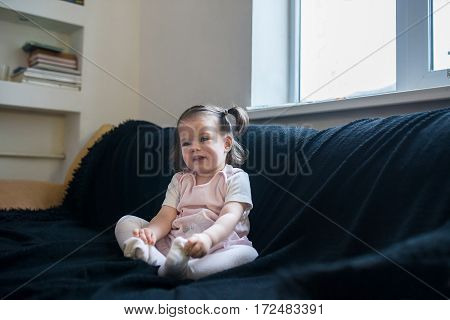 Cute funny baby is sitting in a black chair at home. Nursery and playroom interior for kids.
