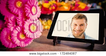 Digital tablet with pink flowers against confident young man against white background