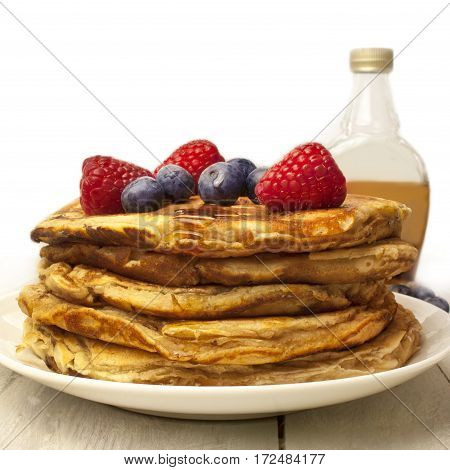 A square photo of freshly baked homemade pancakes, decorated with fresh blueberries and raspberries, with a generic blurred maple syrup bottle in the background, with copy space