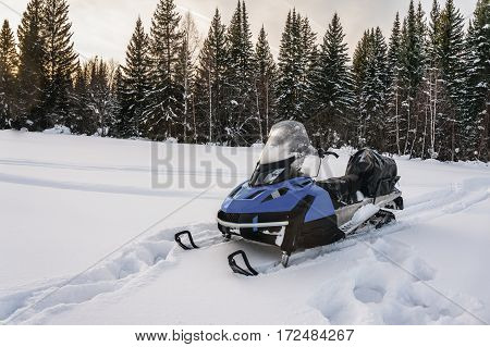 Snowmobile in forest on a snow-covered meadow