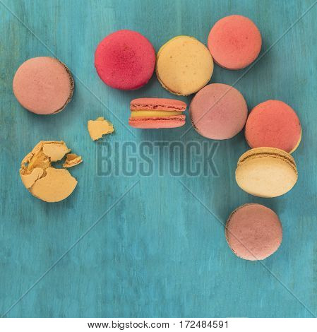 A square photo of various macarons, shot from above on a vibrant blue background texture, with crumbs and copyspace