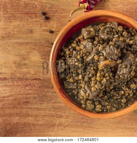 A square photo of a lentil stew, shot from above on a dark wooden texture with bay leaves and peppercorns scattered around it, with copyspace