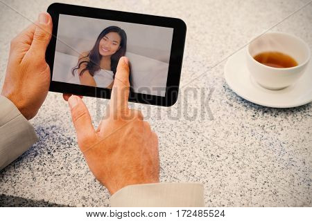 Businessman using small tablet at table against smiling woman lying on bed against wall