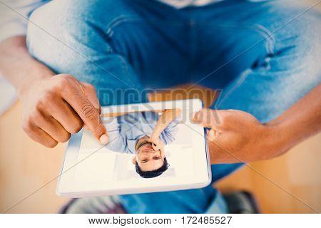 Confident businessman sitting at desk against businessman using digital tablet in creative office