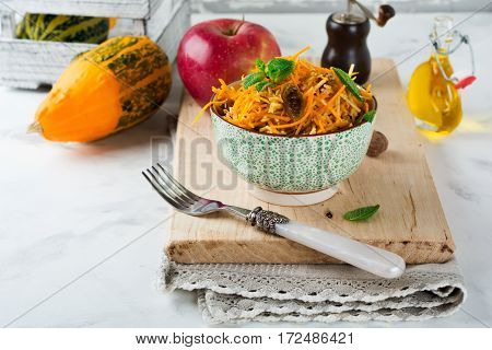 Vegetarian salad with pumpkin apples and raisins on a light background. Selective focus.