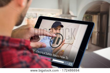 Man using tablet on wooden table against portrait of handyman fixing alarm system