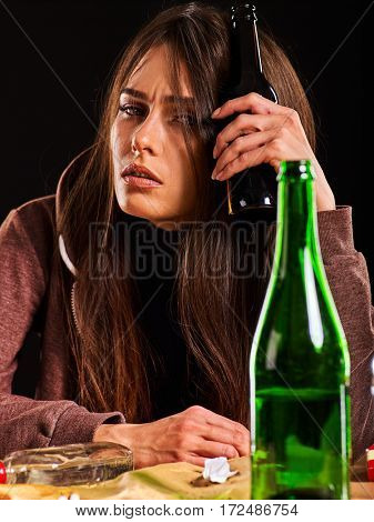 Woman alcoholism is social problem. Female drinking is cause of nervous stress . She in hood and hat with green alcohol bottle in bad mood . Black background as symbol of depression.