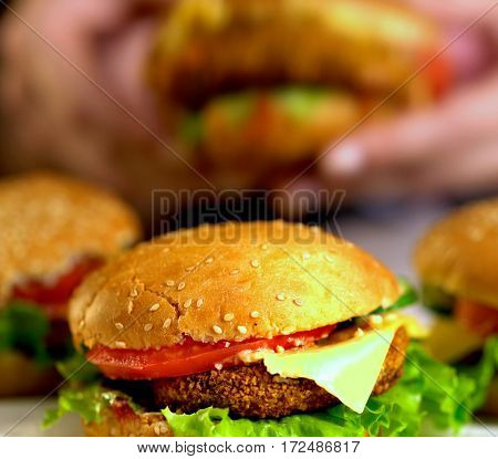 Hamburger fast food with ham on wooden board . Group of hamburger. Human hand holding cheeseburger is not in field.