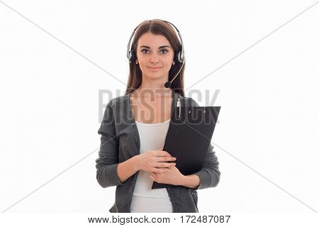 cute young girl looks right standing with headphones and holding a Tablet for securities is isolated on a white background