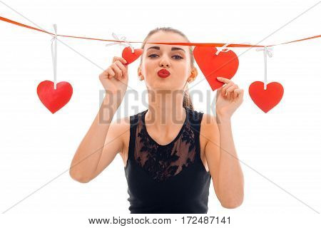 cute young girl sends kiss and keeps the Ribbon with hearts isolated on white background