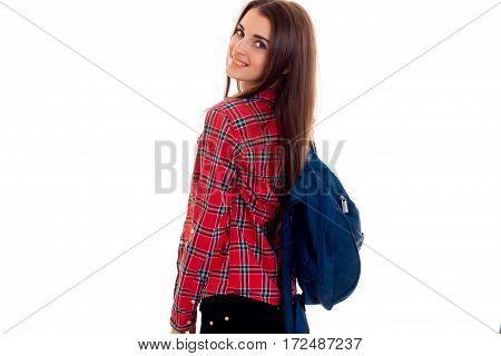cute young girl with a backpack and a Plaid Shirt is worth turning back forward isolated on white background