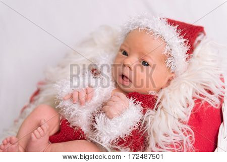Lovely infant dressed as a Santa Claus lying on a soft red fluffy pillow