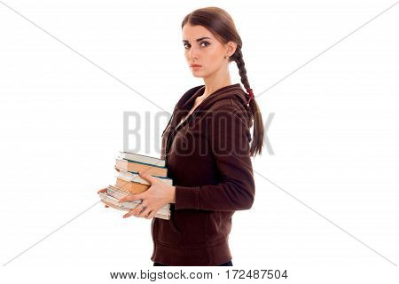 young girl with thoughtful person stands sideways and holding books isolated on white background