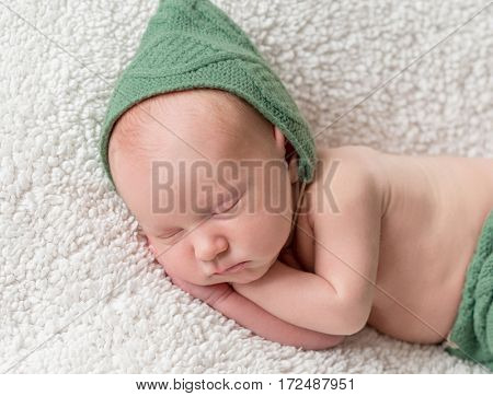 cute newborn sleeping in green elf hat and panties on soft white blanket close-up