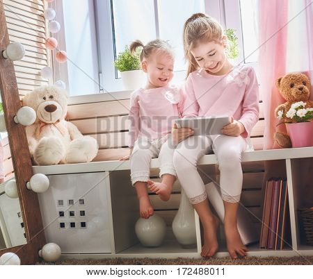 Cute little children are playing with tablet. Happy girls at home. Funny lovely sisters are having fun in kids room.
