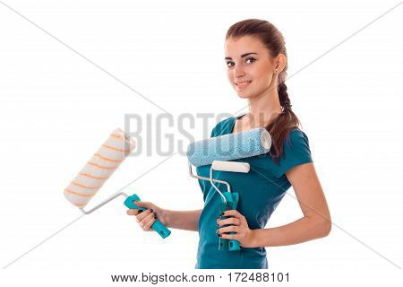 a young girl stands sideways and holding rollers for painting walls isolated on white