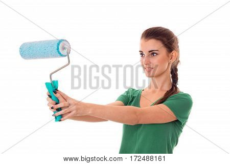 a young girl stands sideways and stretched in the hands of the roller for painting walls close-up isolated on white