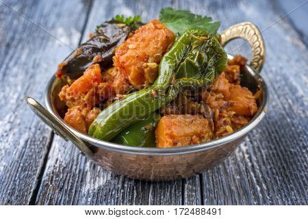 Indian Vegetable Curry Fry with Sweet Potatos and Eggplant as close-up in a Kadai