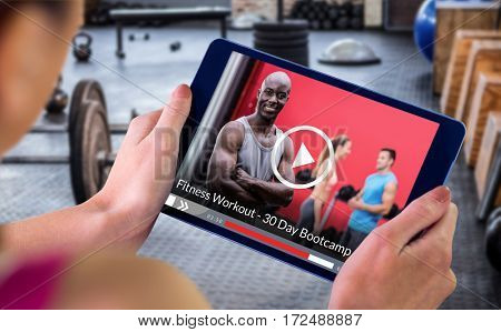 Woman using tablet pc against portrait of muscular man with arms crossed