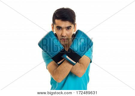 young guy stands folded arms in blue boxing gloves is isolated on a white