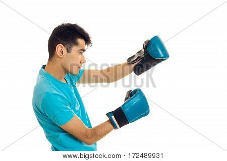 a young guy in a blue t-shirt stands sideways in boxing gloves is isolated on a white