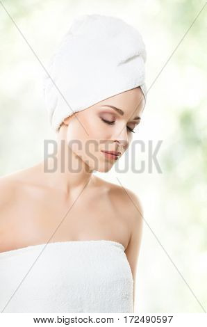 Close-up portrait of beautiful, fresh, healthy and sensual girl with bath towel on her head. Health, treatment, spa concept.