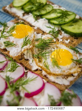 Toast with fried quail eggs and fresh vegetables.