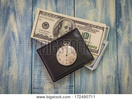 Time is money. photo concept. Pocket watch, wallet and dollar bills