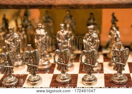 Chess board with chess metal pieces on a background